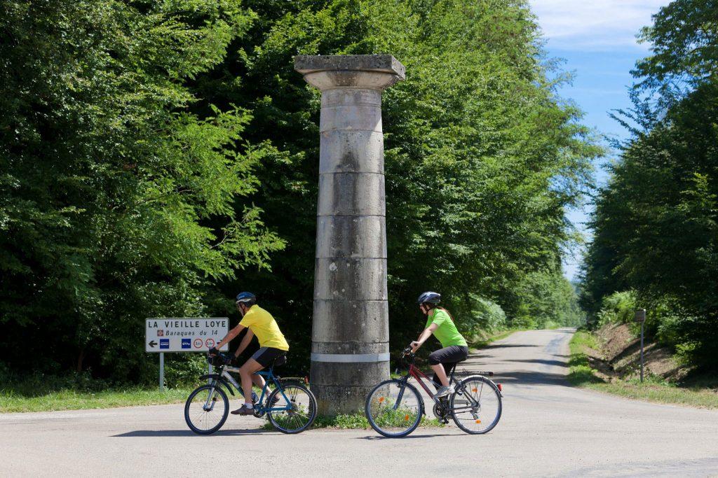 En vélo devant les colonne Guidon en forêt de Chaux © Stéphane Godin/Jura Tourisme