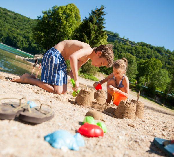 Enfants jouant dans le sable au lac de Chalain
