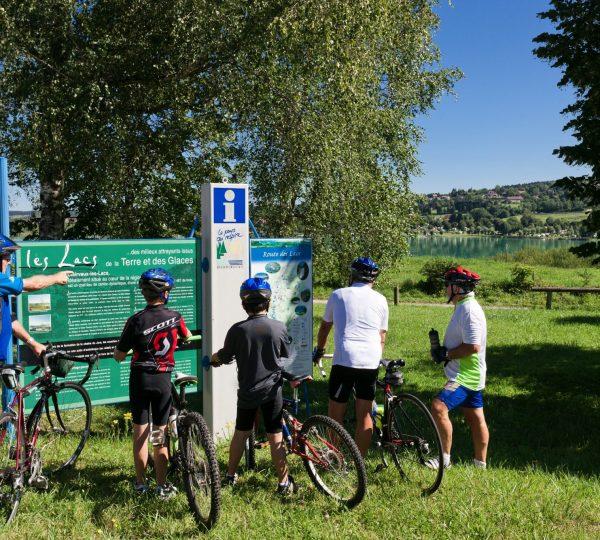 Cyclistes devant un panneau d'information