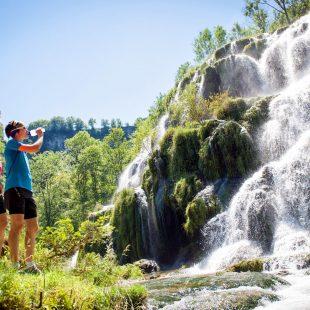Traileuses devant la cascade de tufs de Baume-les-Messieurs