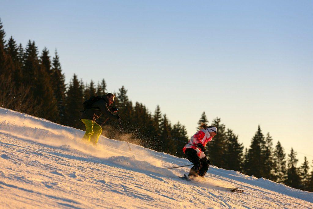 Skieurs en alpin au couché du soleil